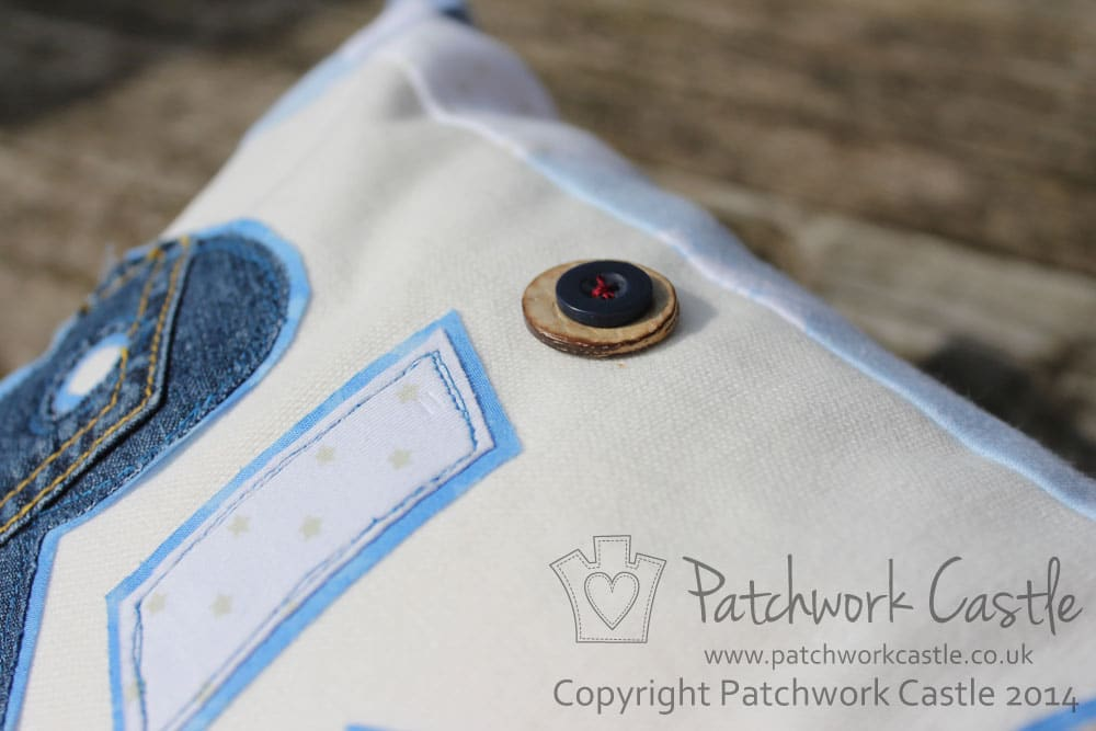 Button detail on personalised keepsake cushion from baby clothes