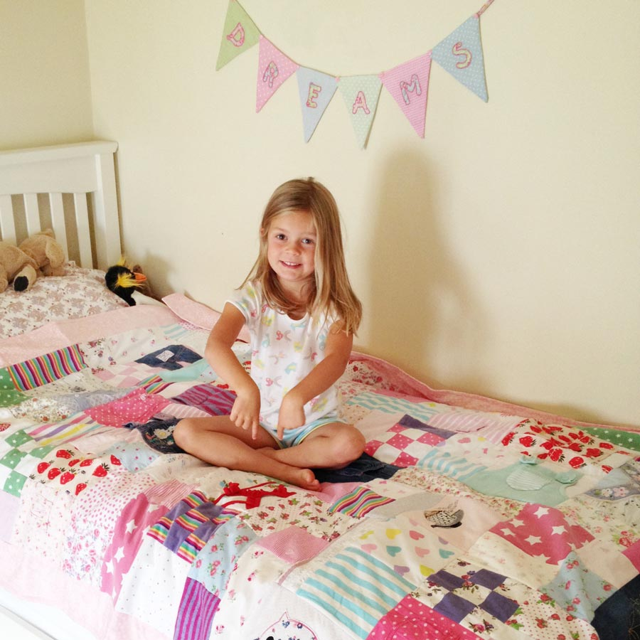 Girl with baby clothes memory quilt
